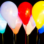 Colorful balloons illuminated with LED against dark background